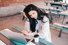 Lovely female businesswoman with dark long hair holding pen in h royalty free stock images