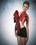 Lovely female christmas gift. Sexy lady posing in lovely christmas portrait adorned like a gift with big red bow on her naked breast, elegant hair-style and Stock Photos