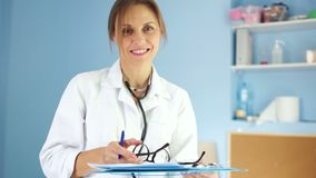 Lovely female doctor in a white medical coat and with a phonendoscope looks into the frame and smiles with a white