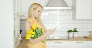 Lovely female with flowers and phone Stock Photo