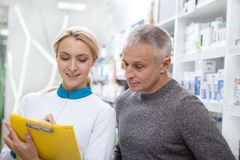 Lovely female pharmacist helping her client stock image