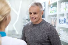 Lovely female pharmacist helping her client royalty free stock images