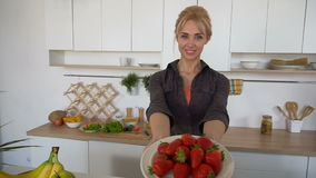 Lovely female posing and smiling at camera with plate of ripe strawberries in modern kitchen. stock footage