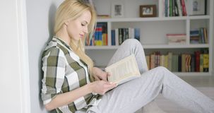 Lovely female reading at home stock video