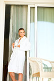 Lovely female standing near big room windows. Lovely female in bathrobe standing near big room windows and having cup of coffee stock photos