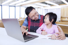 Lovely female student learning with male tutor Stock Photography
