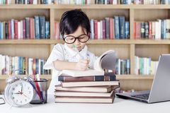 Lovely female student writing in the library Stock Images