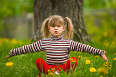 Lovely five-year girl sitting in grass Royalty Free Stock Photo