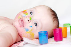 Lovely four-months baby with multi-colored paints Royalty Free Stock Photos