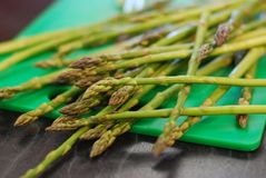 Spears of Asparagus on a chopping board. Lovely fresh and green bunch of asparagus spears ready to be cut up and be cooked royalty free stock images