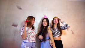 Lovely friendly girls celebrate birthday of their female friends and have fun standing on background of light wall in. Cheerful and beautiful female friends stock footage