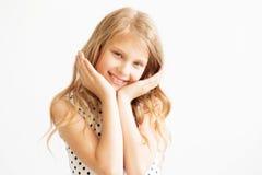Lovely frisky little girl in a polka-dot dress against a white b Royalty Free Stock Images