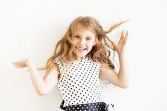Lovely frisky little girl in a polka-dot dress against a white b Stock Images