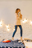 The lovely full-length photo of the young blond girl hugging the teddy bear and jumping on the bed. Royalty Free Stock Photo