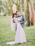 The lovely full-length portrait of the smiling newlyweds hugging in the park. Stock Photography