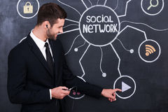 Lovely function for relaxing. Handsome young man in headphones holding telephone while standing against social network chalk drawing on blackboard royalty free stock photos