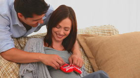 Lovely future parents playing with little shoes Royalty Free Stock Image