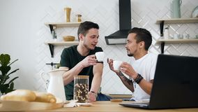 Lovely gay couple fun talking at kitchen in the morning during breakfast time. Roommates drinking coffee together in the. Morning at the kitchen. Slow motion stock video