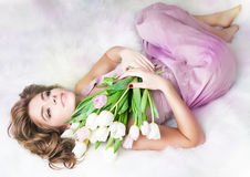 Lovely gentle young woman with bouquet of flowers stock photo