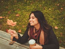 Lovely girl behind wooden table in autumn park Royalty Free Stock Photo