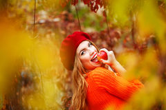 Lovely girl in beret and sweater, holding ripe apple and smiling Royalty Free Stock Photos