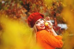 Lovely girl in beret and sweater, holding ripe apple and smiling Stock Image