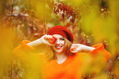Lovely girl in beret and sweater, holding ripe apple and smiling Stock Photos