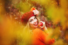 Lovely girl in beret and sweater, holding ripe apple and smiling Stock Photo