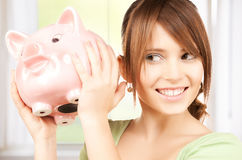 Lovely girl with big piggy bank. Picture of lovely girl with big piggy bank Stock Photography