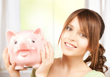 Lovely girl with big piggy bank. Picture of lovely girl with big piggy bank Royalty Free Stock Images