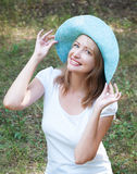 Lovely girl in blue hat on background of forest green Stock Photography