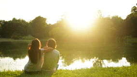 Lovely girl and boy enjoying sunset sitting on the green grass near the lake. Back view of happy couple outdoors. stock footage