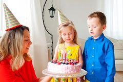 Lovely girl and boy twins in party hats makes a wish before blow out four candles on a birthday cake. Mom smiles and holds a cake. royalty free stock images