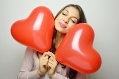 Lovely girl with closed eyes and Valentine heart balloons in her hands. Sweet young woman with two heart shaped balloons Royalty Free Stock Photos