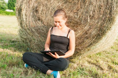 Lovely girl with  device siting close  to haystack Royalty Free Stock Images