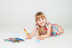 Lovely girl drawing with colorful pencils royalty free stock image