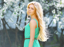Lovely girl in dress in summer. Blooming tree, warm sunny day, beautiful blonde Royalty Free Stock Image