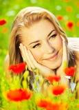 Lovely girl enjoying nature. Lovely happy female closeup portrait, lying down in the poppy flower field, enjoying nature, summertime leisure concept Royalty Free Stock Photos