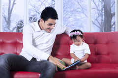 Lovely girl and father read story book Stock Images