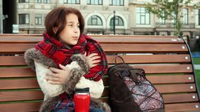 Lovely girl is feeling cold sitting on the bench stock image