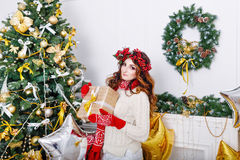 Lovely girl with a gift at Christmas tree stock images