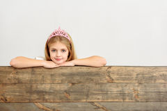 Lovely girl glancing through wood border Royalty Free Stock Image