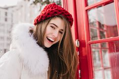 Lovely girl with happy smile posing close to red phone booth in december morning. Outdoor portrait of wonderful european stock image