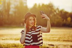 Lovely girl in a hat on the street makes Selfei Stock Images