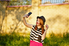 Lovely girl in a hat on the street makes Selfei Royalty Free Stock Images