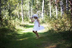 A lovely girl in a hat and sunglasses walks through the forest on a summer sunny day. She runs and dances. Stock Photos