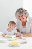 Lovely girl and her grandmother  in a kitchen Royalty Free Stock Image