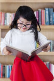 Lovely girl holding a book in library Royalty Free Stock Image