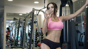 Lovely girl holding bottle of water in gym Royalty Free Stock Image