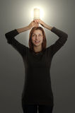 Lovely girl holding a fluorescent lamp over his head Stock Photography